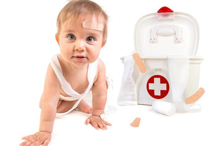 Bebé con botiquín de primeros auxilios
